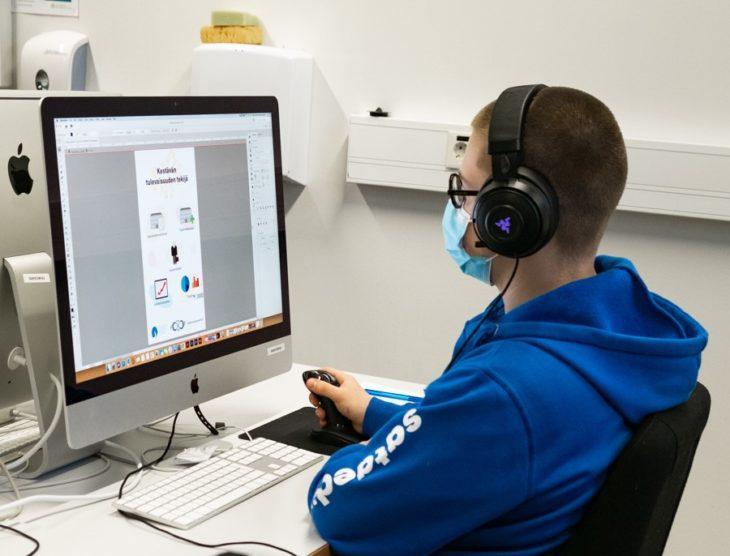 Opiskelija Viljam Alajärvi tekee semifinaalin graafista tehtävää tietokoneella.